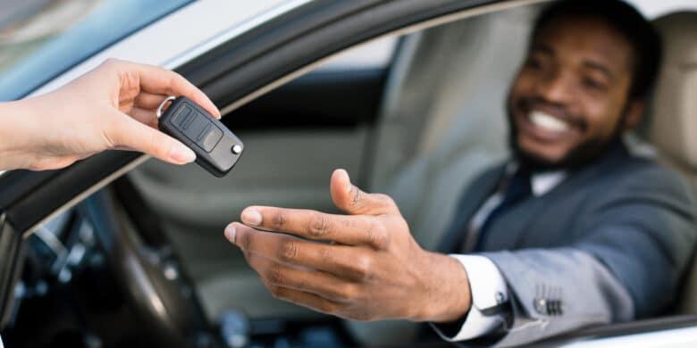Vendeur professionnel donnant les clés au nouveau propriétaire de voiture