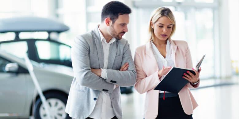 Vendeur professionnel vendant des voitures chez le concessionnaire à l'acheteur