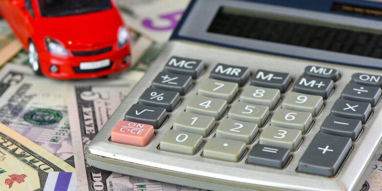 Calculatrice permettant de calculer son financement et voiture rouge jouet sur une variété de billets en monnaie nationale fond